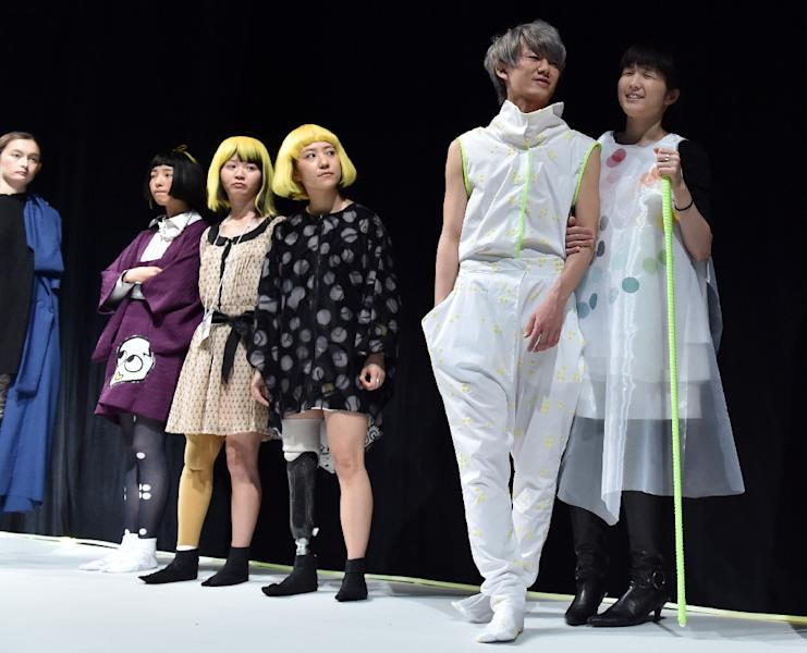 "Blind Paralympic gold medal swimmer Rina Akiyama (R) takes part in rehearsals for a fashion show for ""tenbo"" brand by Japanese designer Takafumi Tsuruta, during Tokyo Fashion Week's 2015-16 autumn/winter collection on March 18, 2015 (AFP Photo/Yoshikazu Tsuno)"