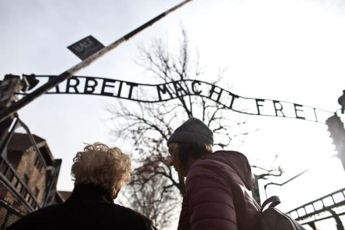 """Jona Laks, survivor of Dr. Josef Mengele's twins experimentsand her granddaughter, Lee Aldar stand next to the gate with the slogan """"Arbeit macht frei"""" (""""Work sets you free"""") as they start their visit at the Auschwitz death camp in Oswiecim"""