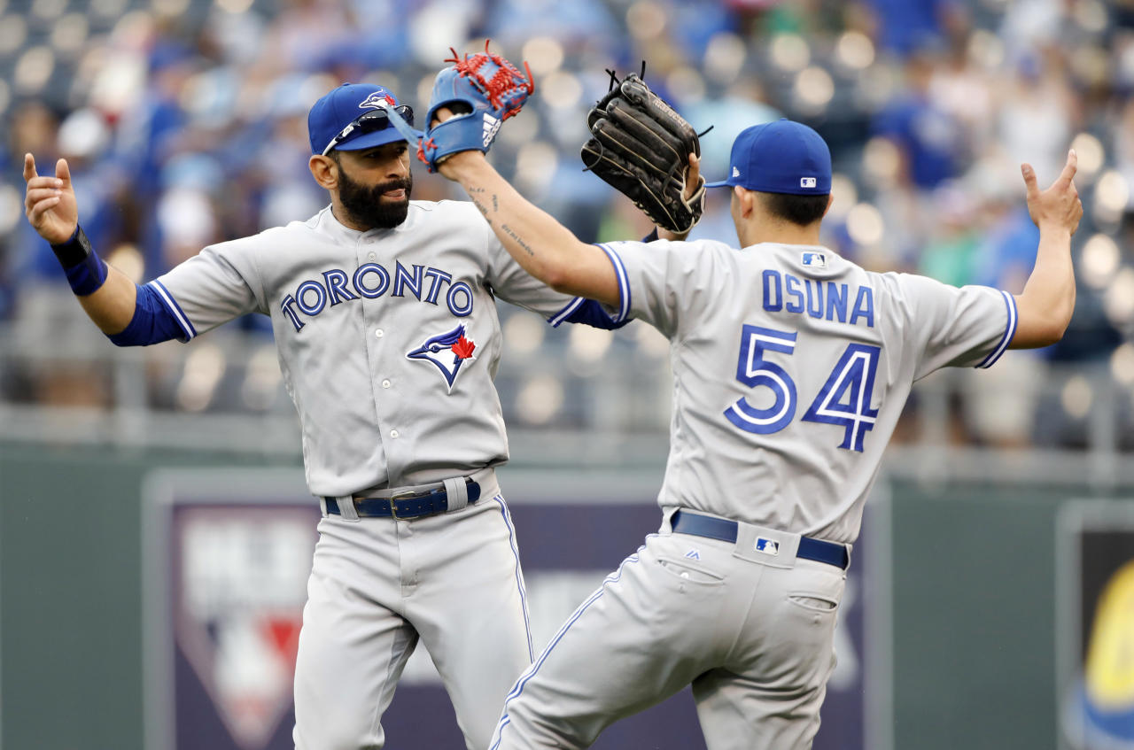 Toronto Blue Jays' Jose Bautista, left, and pitcher Roberto Osuna, right, celebrate at the end of a baseball game against the Kansas City Royals at Kauffman Stadium in Kansas City, Mo., Sunday, June 25, 2017. (AP Photo/Colin E. Braley)