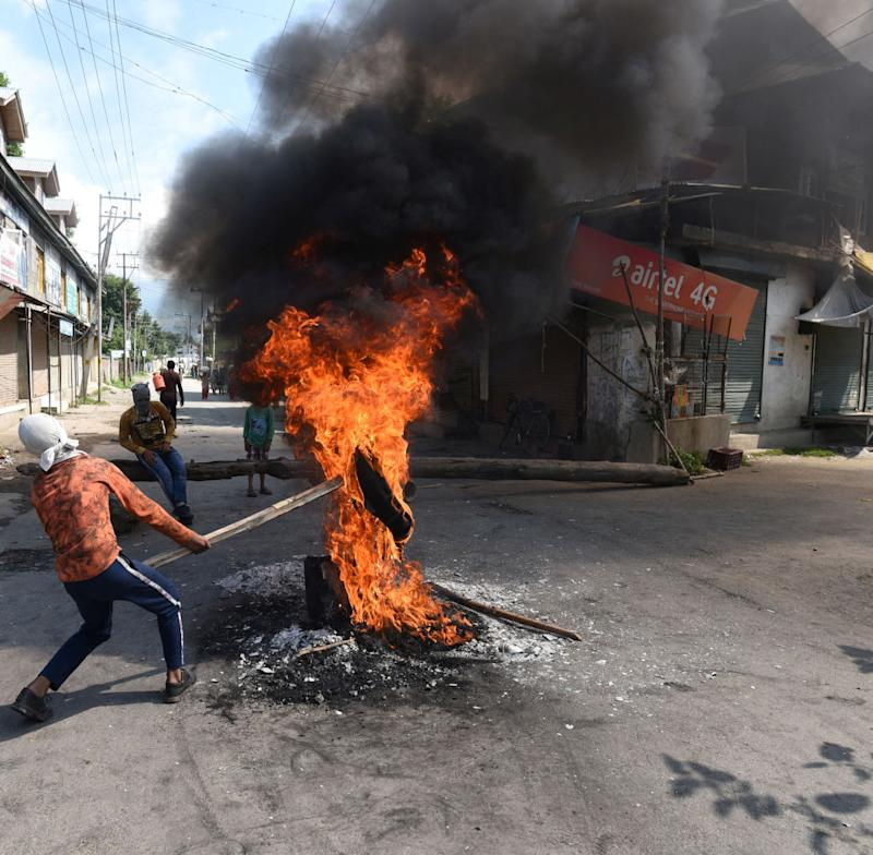 A protester holds a burning tire near a barricade set by the local protesters to block the road during a protest against the abolishing of Article 370, on August 20, 2019 on the outskirts of Srinagar, India. | Waseem Andrabi/Hindustan Times—Getty Images