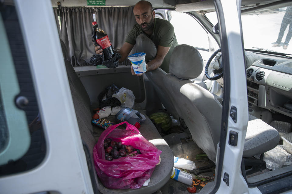 Palestinian Moayyad al-Alami, father of slain Mohammed al-Alami, 12, displays the blood stained grocery left behind at his bullets shattered vehicle, in the West Bank village of Beit Ummar, near Hebron, Wednesday, Aug. 4, 2021. (AP Photo/Nasser Nasser)