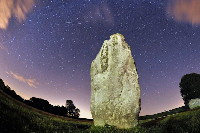 A meteor is seen during the Perseids meteor shower over the one of the stones of the Avebury's Neolithic henge monument in Wiltshire.