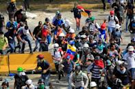 Demonstrators run while clashing with riot security forces during a rally against Venezuela's President Nicolas Maduro in Caracas, Venezuela, May 31, 2017. REUTERS/Christian Veron