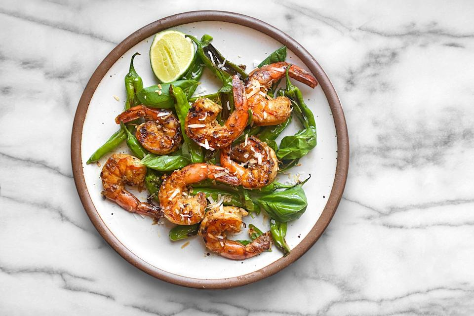 "A garlicky soy sauce marinade helps big flakes of coconut stick to these quick-cooking grilled shrimp. <a href=""https://www.epicurious.com/recipes/food/views/grilled-coconut-shrimp-shishito-peppers?mbid=synd_yahoo_rss"" rel=""nofollow noopener"" target=""_blank"" data-ylk=""slk:See recipe."" class=""link rapid-noclick-resp"">See recipe.</a>"
