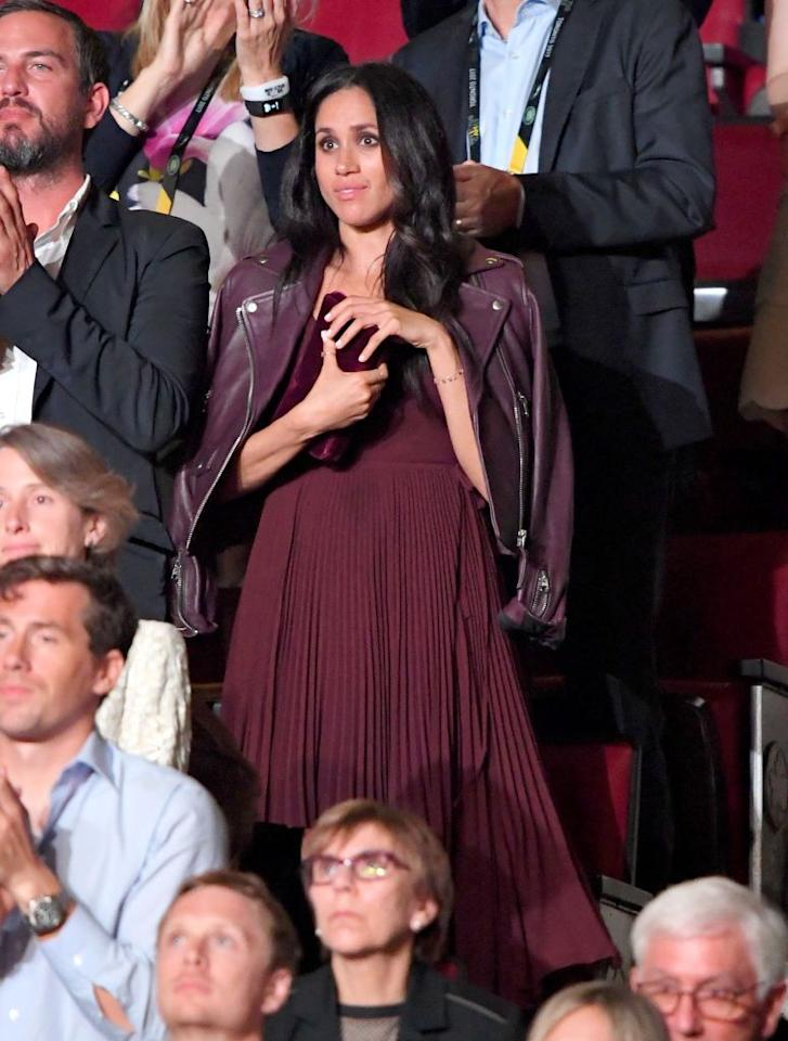 """<p>Meghan Markle attended the Invictus Games Ceremony on Saturday. It was also the <a href=""""https://www.townandcountrymag.com/society/tradition/a12458002/meghan-markle-prince-harry-invictus-games-toronto/"""" target=""""_blank"""">first time she accompanied Prince Harry during an official royal appearance</a>—though they were seated yards away from each other. Markle wore a mulberry-toned, pleated dress from Aritzia's Wilfred brand, priced at just $185. On top, she donned a Mackage leather jacket of the same color, and carried with her a velvet plum clutch.</p>"""