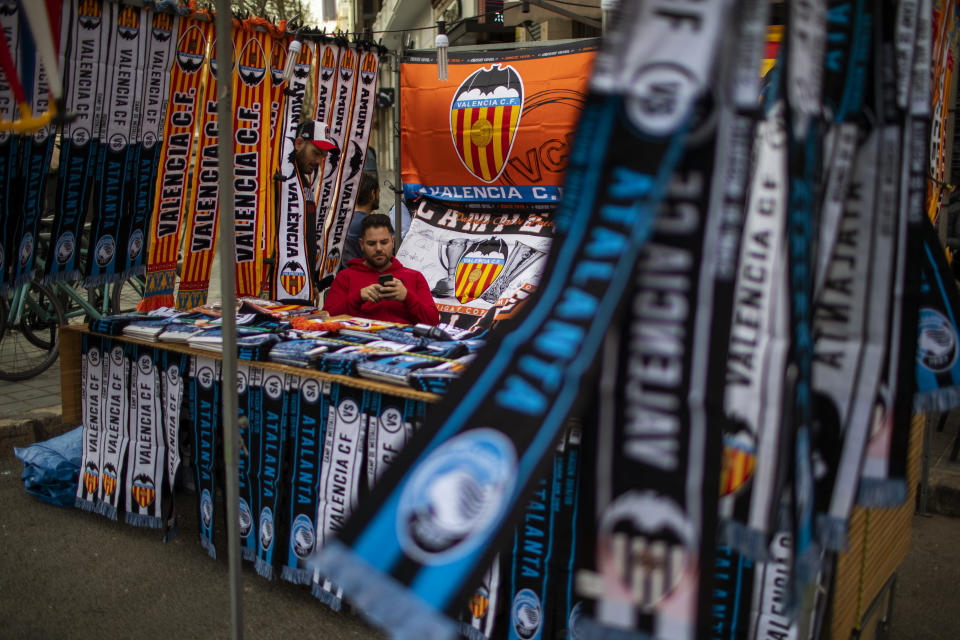 A vendor waits for customers at his stall street outside Mestalla stadium, ahead of the Champions League round of 16 second leg soccer match between Valencia and Atalanta in Valencia, Spain, Tuesday March 10, 2020. The match will take place in an empty stadium because of the coronavirus outbreak. (AP Photo/Emilio Morenatti)