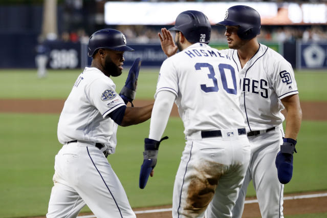 San Diego Padres' Manuel Margot, left, celebrates with Eric Hosmer (30) and Hunter Renfroe, right, after all three scored on a double by Luis Urias during the first inning of the team's baseball game against the Tampa Bay Rays on Tuesday, Aug. 13, 2019, in San Diego. (AP Photo/Gregory Bull)