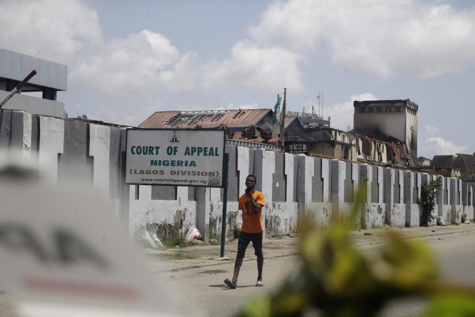 A man walks past a burnt Court of Appeal building in Lagos, Nigeria, Thursday Oct. 22, 2020. Lagos streets were empty and shops were shuttered Thursday, as residents of Nigeria's largest city obeyed the government's curfew, stopping the protests against police brutality that had lasted for two weeks. ( AP Photo/Sunday Alamba)