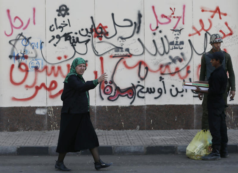 """A woman walks past Arabic writings on a wall that read, """"no, leave, Muslim Brotherhood,"""" in front of the presidential palace in Cairo, Egypt, Thursday, Dec. 13, 2012. Egypt's opposition called on its followers to vote """"no"""" in a crucial referendum on a disputed constitution drafted by Islamist supporters of President Mohammed Morsi. (AP Photo/Hassan Ammar)"""