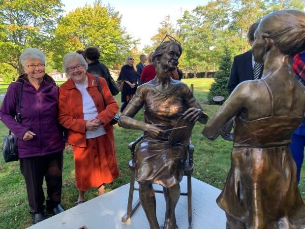 Knitters Florence Rose, left, and Yvonne Sheppard stand next to a new statue commemorating 100 years of NONIA at Government House in St. John's. (Heather Barrett/CBC - image credit)