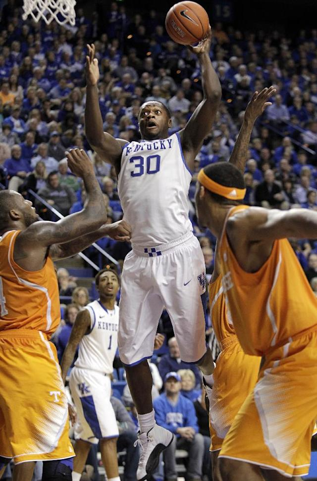 Kentucky's Julius Randle (30) shoots as Tennessee's Jeronne Maymon, left, and Tennessee's Jarnell Stokes defend during the second half of an NCAA college basketball game, Saturday, Jan. 18, 2014, in Lexington, Ky. Kentucky won 74-66. (AP Photo/James Crisp)