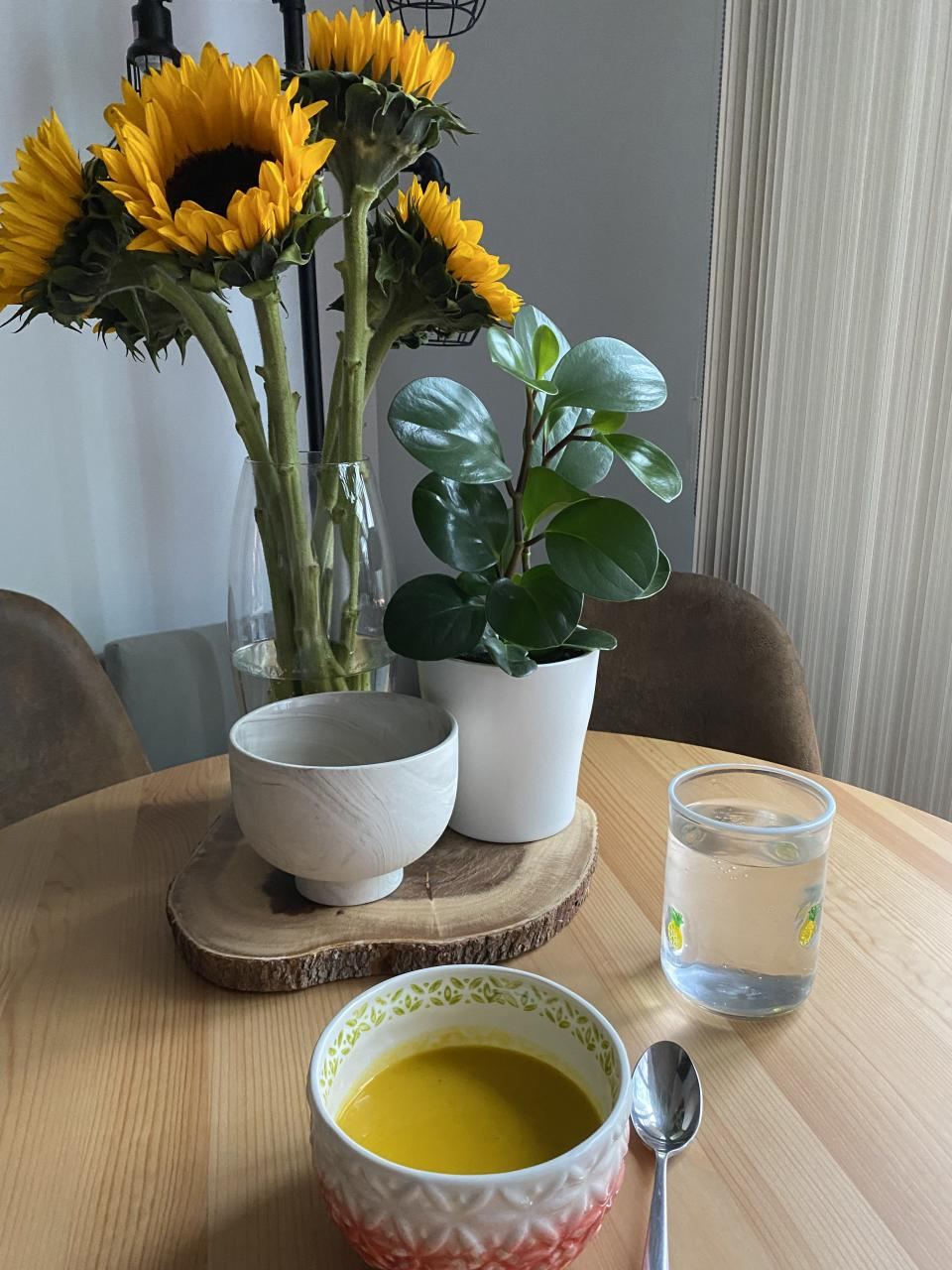 sunflowers, candle and bowl of orange soup