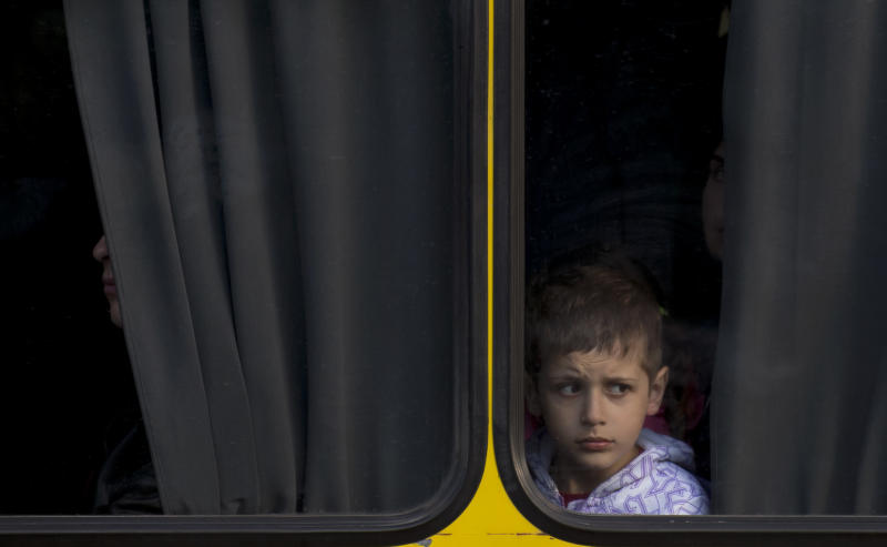 A child looks from inside a bus in Odessa, Ukraine, Tuesday, May 13, 2014. Pro-Russian separatists in Eastern Ukraine held a referendum Sunday and claimed that about 90 percent of those who voted in Donetsk and Luhansk backed sovereignty. The two regions declared independence on Monday and insurgents in Donetsk even asked to join Russia. (AP Photo/Vadim Ghirda)