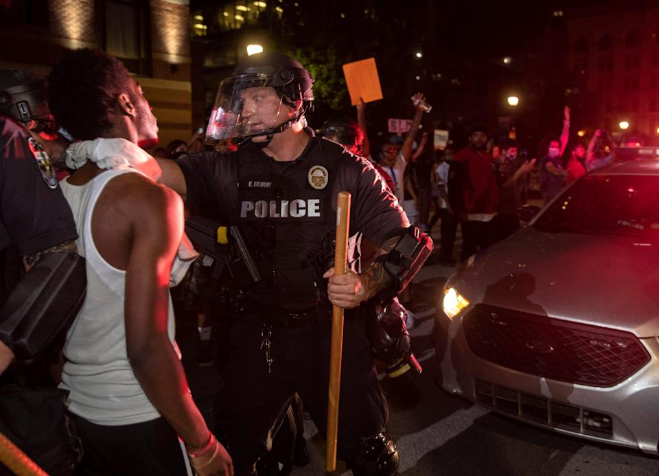 Louisville Metro police and protesters face off last May as police attempt to remove patrol cars from the crowd.