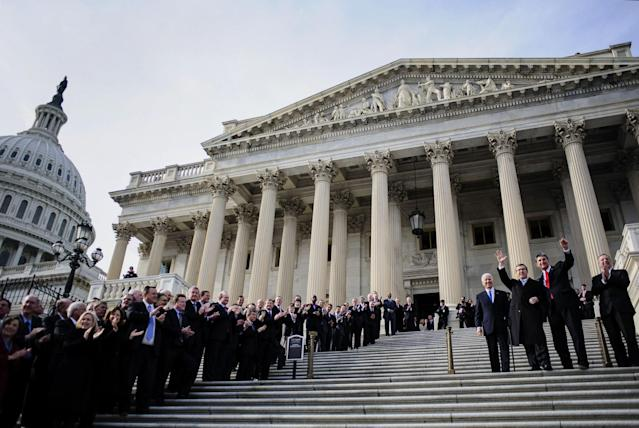 Sen. Mark Kirk, R-Ill., second from left, and Sen. Joe Manchin, D-W.Va., second from right, wave at the Capitol in 2013. (Photo: Pete Marovich/Bloomberg via Getty Images)