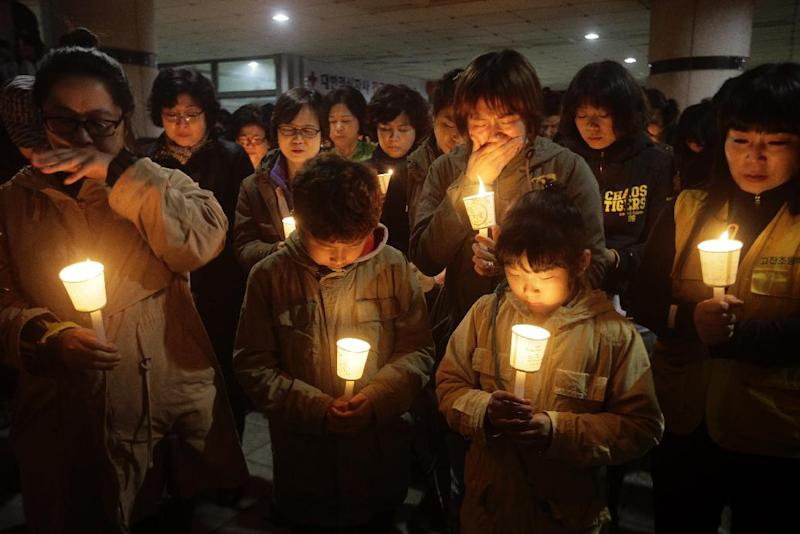 People gather to pray with candlelights for the missing passengers of a sunken ferry at Danwon High School in Ansan, South Korea, Thursday, April 17, 2014. An immediate evacuation order was not issued for the ferry that sank off South Korea's southern coast, likely with scores of people trapped inside, because officers on the bridge were trying to stabilize the vessel after it started to list amid confusion and chaos, a crew member said Thursday. (AP Photo/Woohae Cho)