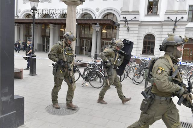 Police officers secure the area outside Stockholm Central station, on April 7, 2017 after a truck crashed into department store Ahlens on Drottninggatan, in central Stockholm