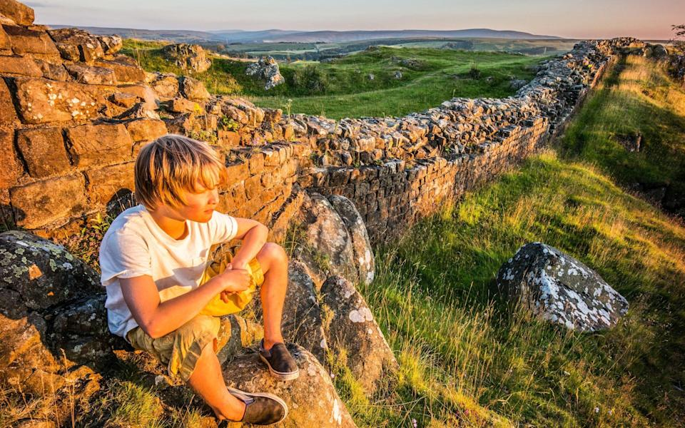 boy sitting by hadrian's wall - Getty