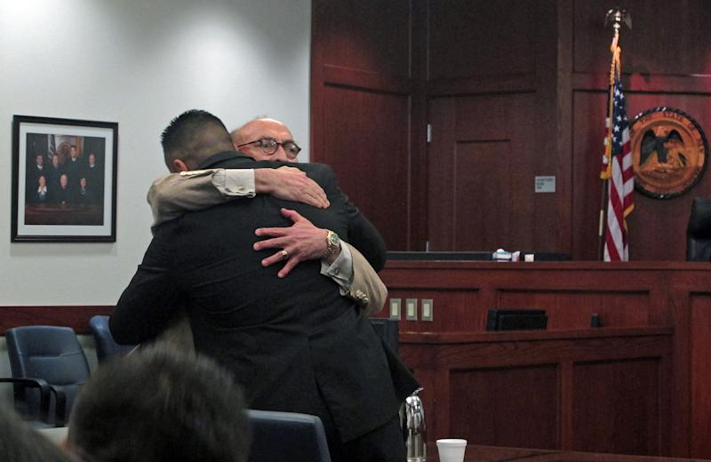 In this July 16, 2013 photo, Levi Chavez, 32, left, hugs his defense attorney, David Serna, in Sandoval District Court in Bernalillo, N.M., after a jury acquitted him of murdering his wife, 26-year-old Tera Chavez, in 2007 and making it look like a suicide. The jury's decision came after more than 10 hours of deliberations and a month long trial detailing Chavez's many affairs, charges of a botched investigation and allegations of a police cover-up. (AP Photo/Russell Contreras)