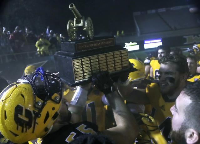 Central Michigan football players hold the Victory Cannon trophy after their NCAA college football game against Western Michigan, Wednesday, Nov. 1, 2017, in Kalamazoo, Mich. The Victory Cannon is awarded to the winner of the in-state rivalry. (AP Photo/Carlos Osorio)