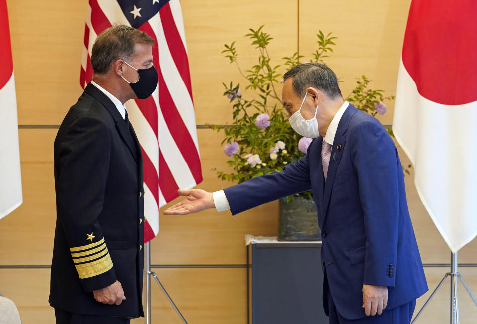 Admiral John C. Aquilino, left, Commander of the United States Indo-Pacific Command, is welcomed by Japanese Prime Minister Yoshihide Suga at the start of their meeting at the prime minister's official residence in Tokyo, Japan, Tuesday, June 1, 2021. (Franck Robichon/Pool Photo via AP)