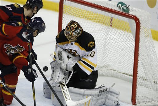 Boston Bruins goalie Tuukka Rask, right, stops the puck as Florida Panthers center Shawn Matthias, left, and Stephen Weiss, center, look on during the second period of an NHL hockey game, Monday, Jan. 16, 2012, in Sunrise, Fla. (AP Photo/Lynne Sladky)
