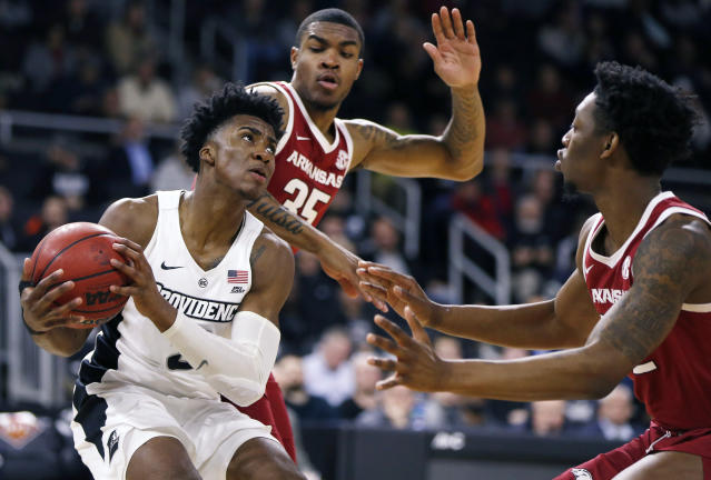 Providence's David Duke, left, goes up to shoot against Arkansas' Reggie Chaney (35) and Gabe Osabuohien, right, during the first half of a first round NCAA National Invitation Tournament college basketball game in Providence, R.I., Tuesday, March 19, 2019. (AP Photo/Michael Dwyer)