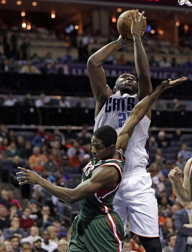 Charlotte Bobcats' Al Jefferson, back, shoots over Milwaukee Bucks' Brandon Knight, front, during the first half of an NBA basketball game, Monday, Dec. 23, 2013, in Charlotte, N.C. (AP Photo/Chuck Burton)