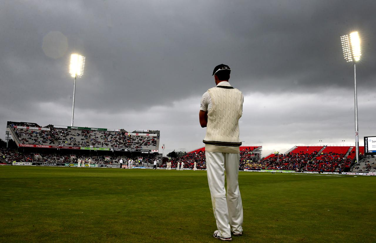 Australia fielder Mitchell Starc stands watching the dark clouds bring rain and stopping play just after lunch during day five of the Third Investec Ashes test match at Old Trafford Cricket Ground, Manchester.