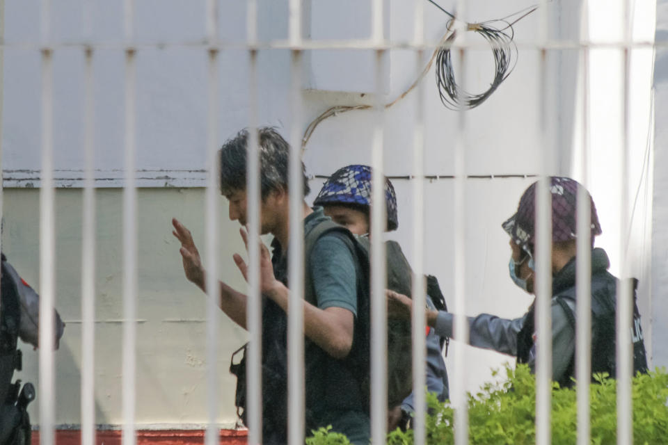 FILE - In this Feb. 26, 2021, file photo, Japanese journalist Yuki Kitazumi raises his hands as he is escorted by police upon arrival at the Myaynigone police station in Sanchaung township in Yangon, Myanmar. Kitazumi returned to Japan on May 14, 2021 after his release. Media and human rights advocates say journalists in Myanmar are in extreme peril as the military-controlled government cracks down on independent reporting. (AP Photo, File)