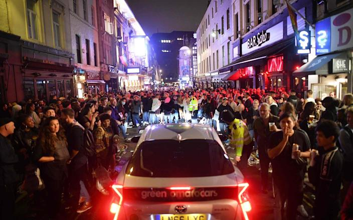 A car tries to drive along a street filled with revellers drinking in the Soho area of London - JUSTIN TALLIS / AFP
