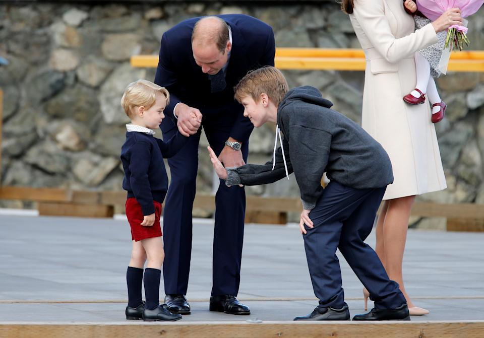 Daniel Bachman (R), 11, who presented flowers to the Royal family, tries to high-five Britain's Prince George (L) while Prince William looks on as they arrive to board a floatplane for their official departure from Canada in Victoria, British Columbia, Canada, October 1, 2016. REUTERS/Chris Wattie     TPX IMAGES OF THE DAY