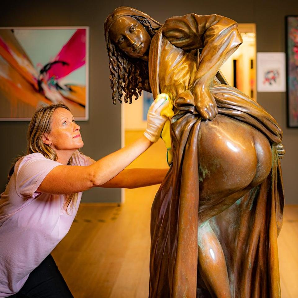 Vanguard exhibition director Mary McCarthy polishes the life-sized bronze artwork (PA) (PA Wire)