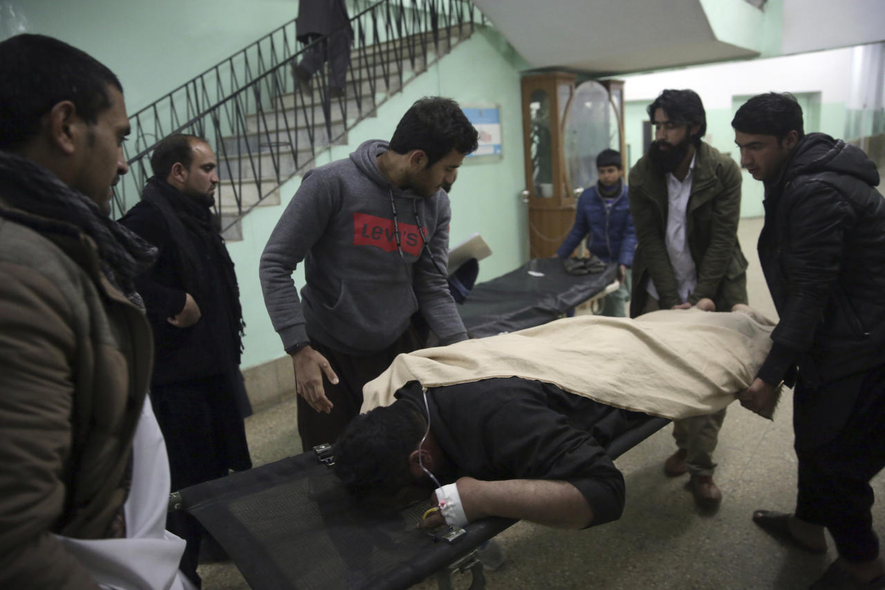 Men assist a wounded relative in a hospital in Kabul, Afghanistan, Monday, Jan. 14, 2019. Afghan officials say multiple people were killed when a suicide bomber detonated a vehicle full of explosive in the capital Kabul on Monday. (AP Photo/Massoud Hossaini)