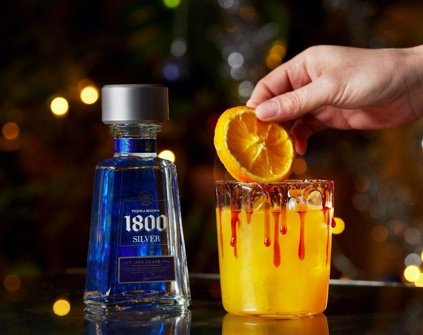 """<p>Dip the rim of your glass in Christmas Glaze. Add 4 cloves into your cocktail shaker and smash into smaller pieces with a muddler. Add 50ml <a href=""""https://www.amazon.co.uk/1800-Tequila-Silver-70-cl/dp/B008O42DO0/ref=sr_1_5?dchild=1&keywords=1800+Silver+Tequila&qid=1607533268&quartzVehicle=705-1272&replacementKeywords=1800+tequila&sr=8-5"""" rel=""""nofollow noopener"""" target=""""_blank"""" data-ylk=""""slk:1800 Silver Tequila"""" class=""""link rapid-noclick-resp"""">1800 Silver Tequila</a>, 25ml Cranberry Juice, 1⁄2 a Fresh juiced orange and 12.5ml salted rosemary syrup. Fill your cocktail shaker with ice & shake hard for 10 seconds. Finally, pour the liquid through a strainer into your glass. Garnish with a dehydrated orange wheel and enjoy! <br></p>"""