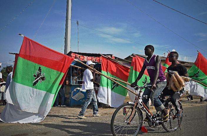 People cycle past supporters carrying flags of the ruling party, CNDD FDD (National Council for the Defense of Democracy–Forces for the Defense of Democracy), in Bujumbura on May 17, 2015 (AFP Photo/Carl de Souza)