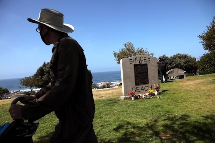 MANHATTAN BEACH, CA - APRIL 9 - - A pedestrian walks past a marker that gives the history of Bruce's Beach in Manhattan Beach on April 9, 2021. Los Angeles Supervisor Janice Hahn announced that the process of returning Bruce's Beach back to the family of Willa and Charles Bruce has begun. Sen. Steven Bradford has created SB 796 that will allow Bruce's Beach to be returned to surviving members of the Bruce family. In 1912, a young Black couple named Willa and Charles Bruce purchased beachfront property in Manhattan Beach and built a beautiful beach resort that served Black residents. It was one of the few beaches where Black residents could go because so many other local beaches did not permit Black beachgoers. The Bruce's and their customers were harassed and threatened by white neighbors including the KKK. Eventually, the Manhattan Beach City Council moved to seize the property using eminent domain, purportedly to create a park. The Council took the property in 1929 and it remained empty for many years. The property the Bruce's once owned was years later transferred to the State and in 1995 transferred to Los Angeles County. It is now the site of the Los Angeles County Lifeguard Training Headquarters. APRIL 09: Manhattan Beach Friday, April 9, 2021 Manhattan Beach, CA. (Genaro Molina / Los Angeles Times)