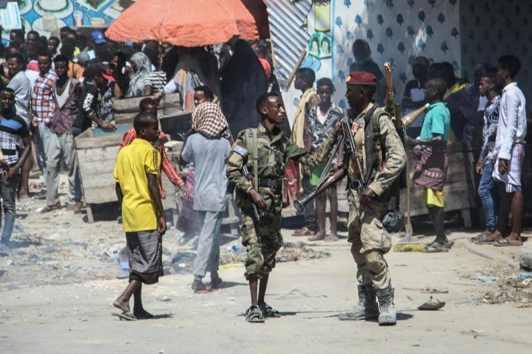 Members of the military force supporting opposition leaders watch over a street in Mogadishu
