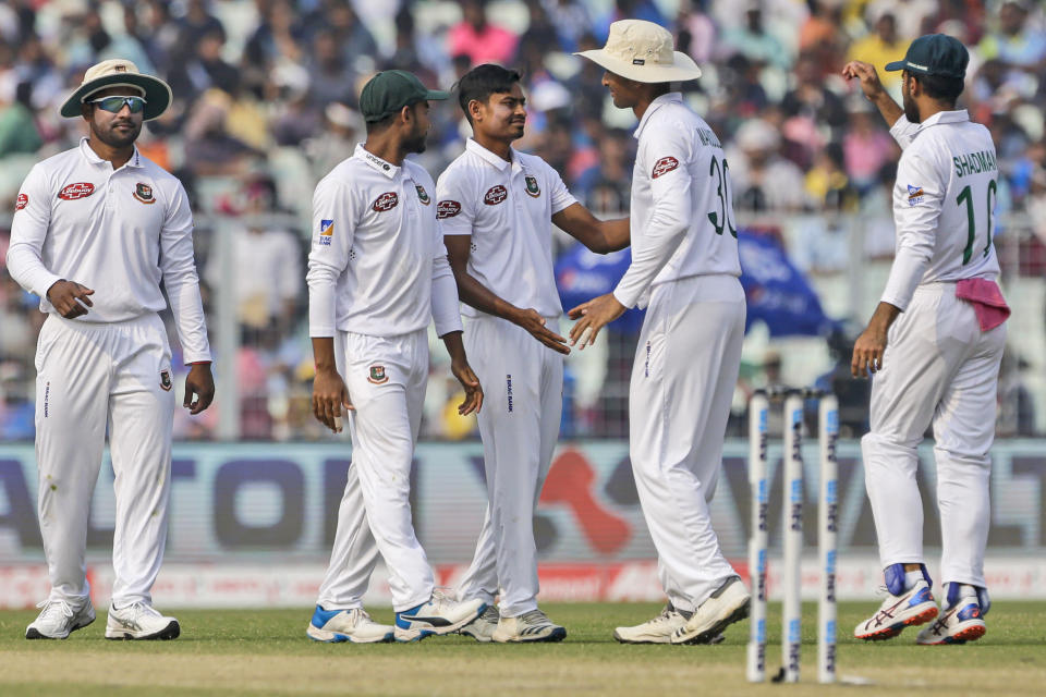 Bangladesh's Taijul Islam, center, is congratulated by teammates after he took the wicket of India's Ajinkya Rahane during the second day of the second test cricket match between India and Bangladesh, in Kolkata, India, Saturday, Nov. 23, 2019. (AP Photo/Bikas Das)