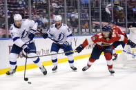 Tampa Bay Lightning defenseman Luke Schenn, left, passes the puck as Florida Panthers left wing Ryan Lomberg, right, defends during the second period of an NHL hockey game, Monday, May 10, 2021, in Sunrise, Fla. (AP Photo/Lynne Sladky)