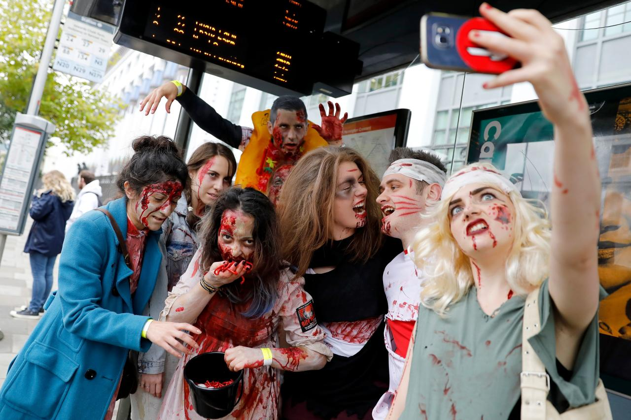 <p>People wearing costumes pose for photograph at a bus stop before participating in a zombie walk on World Zombie Day in London on Oct. 7, 2017. (Photo: Tolga Akmen/AFP/Getty Images) </p>