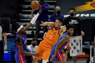 Phoenix Suns guard Devin Booker (1) passes over Detroit Pistons forward Jerami Grant, left, during the first half of an NBA basketball game, Friday, Feb. 5, 2021, in Phoenix. (AP Photo/Matt York)