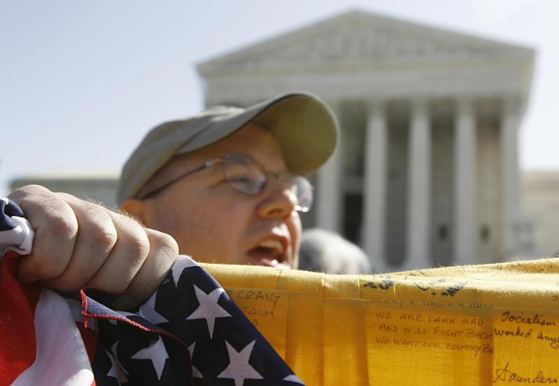 Luke Livingston, from Atlanta, Ga., who opposes the health care reform law signed by President Barack Obama, rallies in front of the Supreme Court in Washington, Monday, March 26, 2012, as the court begins three days of arguments on health care. (AP Photo/Charles Dharapak)