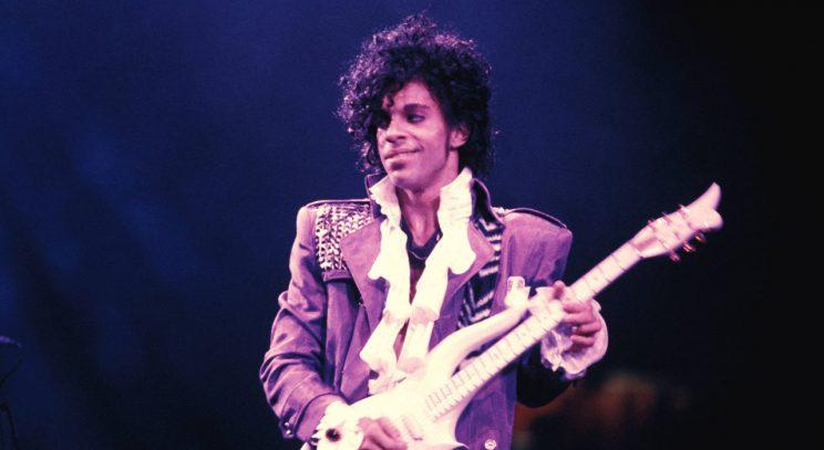 Prince performs with a guitar.