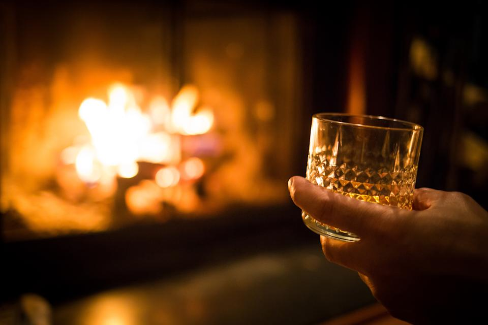 Hand holding whiskey glass at warm fireplace