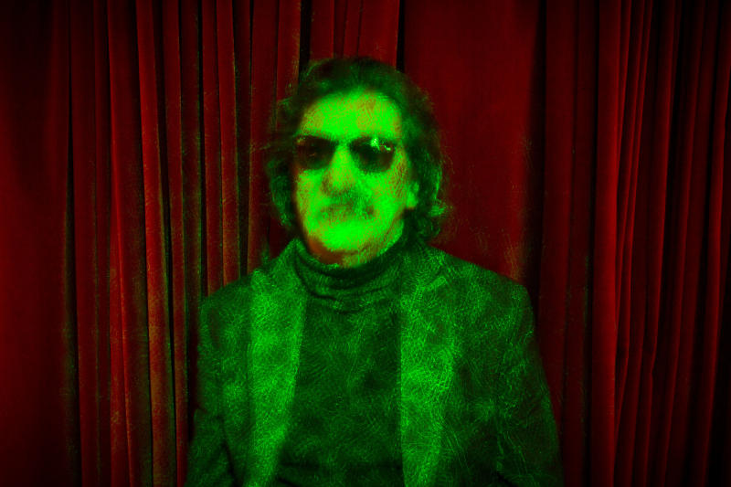 Argentine rock legend Charly Garcia poses for a portrait bathed in green laser lights in Buenos Aires, Argentina, Wednesday, Aug. 14, 2013. Garcia, who is 61 and has a vast career that defined and inspired the rock and pop music world in Latin America, will perform two shows at Teatro Colon, Argentina's landmark opera house, on Sept. 23 and 30. (AP Photo/Victor R. Caivano)