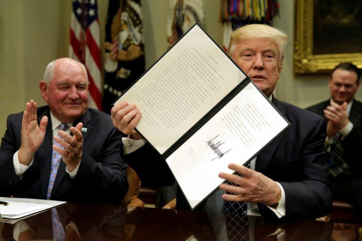 President Trump shows off a signed executive order. (Photo: Yuri Gripas/Reuters)