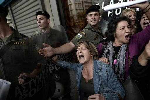 <p>Protesters are pushed back from the riot police as EU and IMF officials escorted out from the emergency exit of the Greek Finance Ministry after their meeting with the Greek Finance Minister in Athens on November 5, 2013</p>
