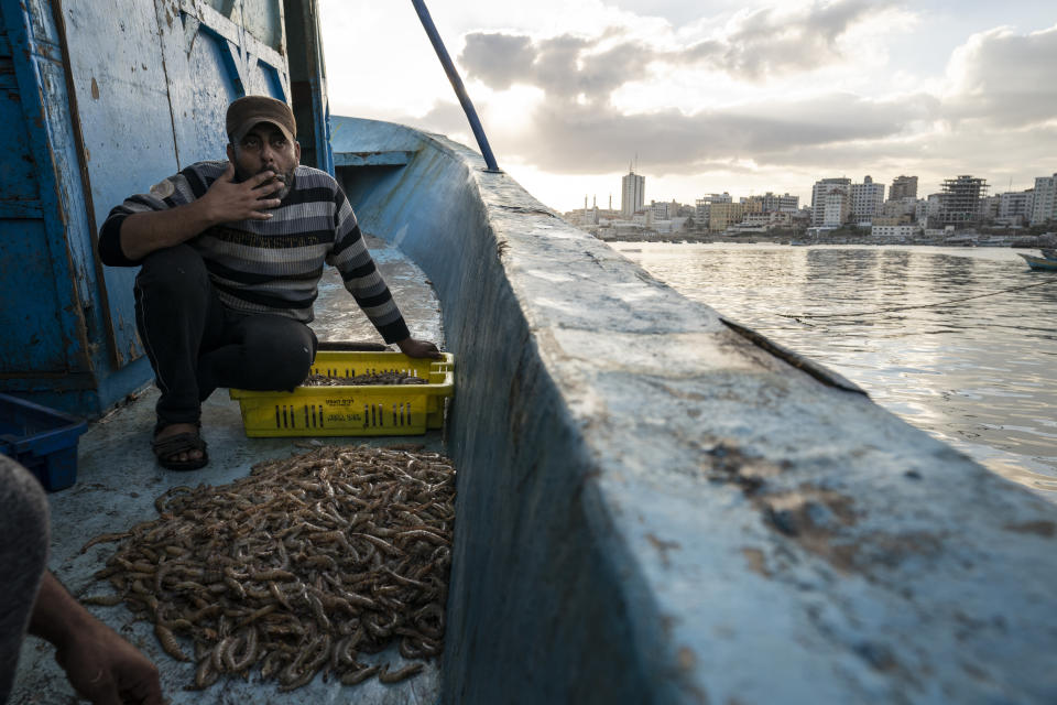 A fisherman takes a drag from his cigarette while sorting shrimp on deck after a limited number of boats are allowed to return to the sea following a cease-fire reached after an 11-day war between Gaza's Hamas rulers and Israel, in Gaza City, Sunday, May 23, 2021. (AP Photo/John Minchillo)