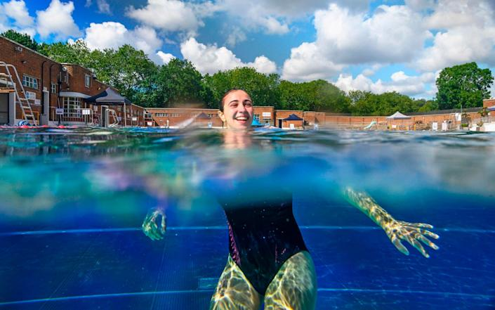A swimmer enjoys the water at Parliament Hill Lido on its reopening today - AFP